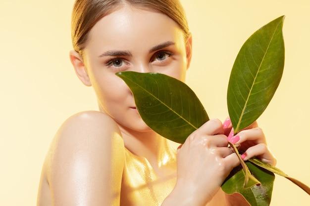 Крупным планом красивая молодая женщина с зелеными листьями на белом фоне