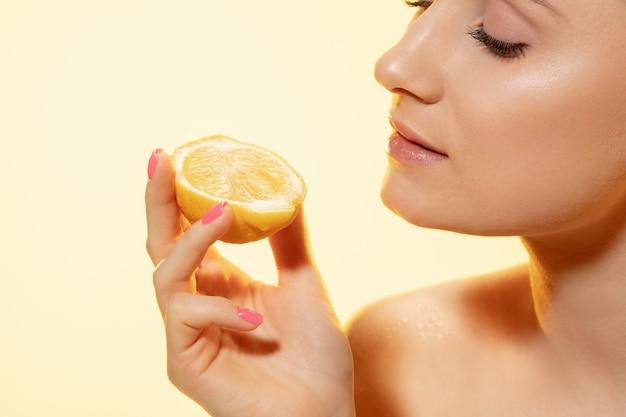 Закройте красивой молодой женщины с ломтиком лимона на желтом фоне. концепция косметики, макияжа, натуральных и экологических процедур, ухода за кожей. блестящая и здоровая кожа, мода, здравоохранение.