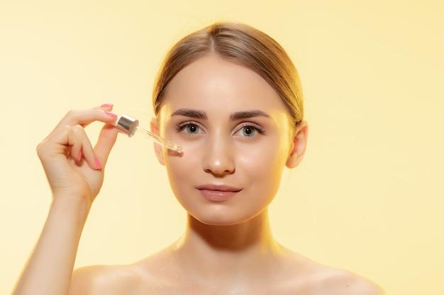 Крупным планом красивой молодой женщины с наливанием масла сыворотки на желтом фоне