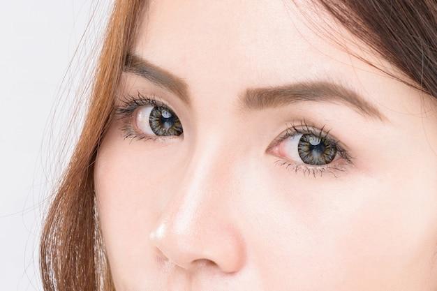 美容アジアの女性の目のクローズアップ、白い背景に分離された美容アジアの女性の顔をクローズアップ
