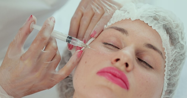현대 미용 클리닉에서 미용 주사 절차의 클로즈업. 여성 뺨에 주사기로 주입. 미용실에서 메조테라피와 얼굴 리프팅 치료를 하는 미용사.