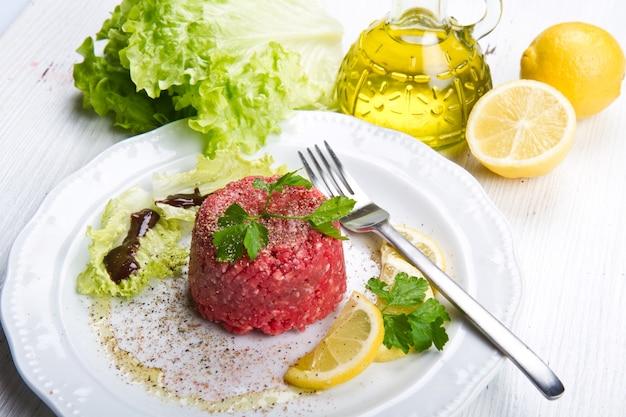 신선한 샐러드와 레몬 슬라이스를 곁들인 쇠고기 타르타르 클로즈업