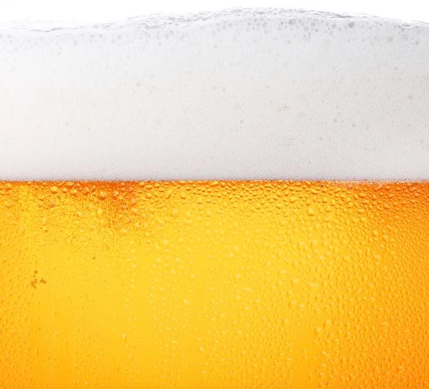 グラスに泡とビールのクローズアップ