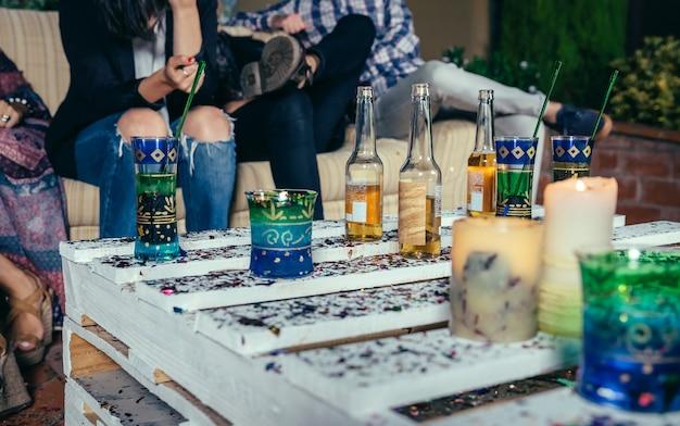 Крупный план напитков над столом из поддонов с конфетти на вечеринке на открытом воздухе с людьми, говорящими на заднем плане