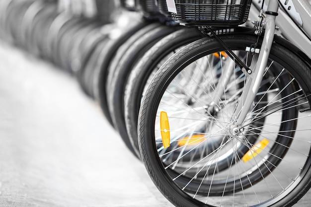 지역 여행 도시에서 운동, 스포츠 및 교통을 위한 렌탈 서비스 및 승차 차량을 위해 차선을 따라 자전거 바퀴와 타이어를 닫습니다.