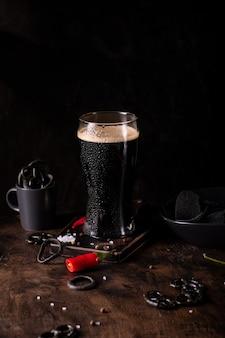 어두운 맥주의 큰 유리, 스낵과 검은 배경에 차가운 스타우트 닫습니다