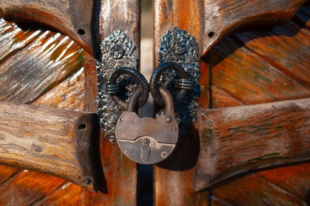 나무 문 큰 빈티지 자물쇠의 클로즈업입니다.