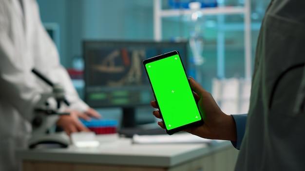 Закройте вверх биохимика, держащего и смотрящего на телефон с дисплеем цветного ключа, стоящего в биологической лаборатории, пока медсестра в белом халате приносит образец крови. ученый, использующий телефон с макетом, зеленый экран