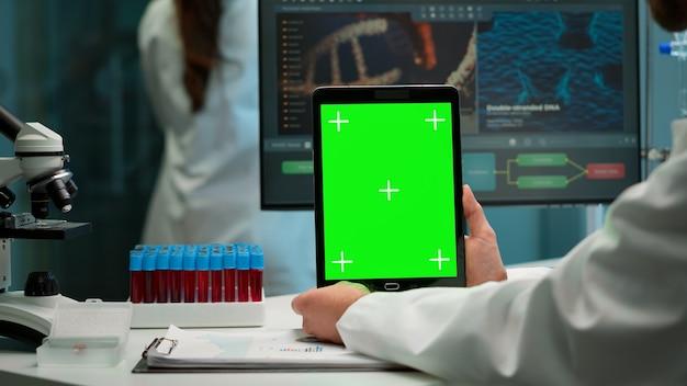クロマキーディスプレイ付きの緑色のモックアップスクリーンタブレットを使用して、実験室の職場に座っている生化学者のクローズアップ。血液サンプルを持ってバックグラウンドで働いている同僚。