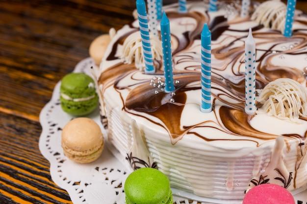 나무 책상 위에 다양한 색깔의 마카롱 근처에 많은 양초가 있는 생일 케이크를 닫아라
