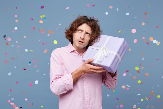 誕生日の男性のクローズアップは贈り物として箱を受け取りました
