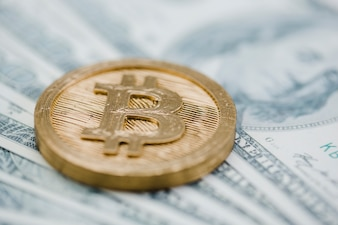 Close-up of bitcoin over the us dollar banknotes
