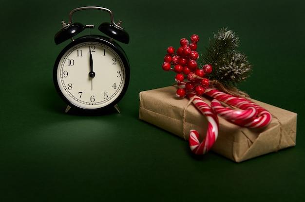 文字盤に真夜中の黒い目覚まし時計、甘い縞模様のロリポップ、キャンディケイン、クリスマスプレゼントのヒイラギのクローズアップ。広告用のコピースペースが付いた緑の背景に分離されたクラフト包装紙