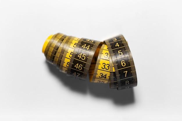 그림자와 흰 배경에 고립 된 검정색과 노란색 측정 테이프의 근접
