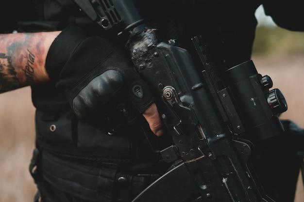 コリメータ照準器を備えた黒いアサルトライフルのクローズアップ