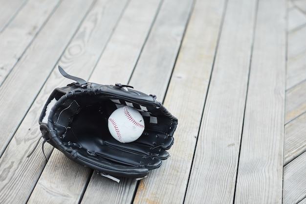 木の表面にボールを置いた黒い野球ミットのクローズアップ
