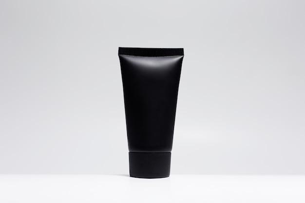 白い表面に分離されたモックアップと黒のクリーム色のチューブのクローズアップ