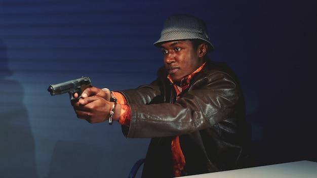 銃を掴んで警官に危害を加えると脅迫している黒人の犯罪者のクローズアップ