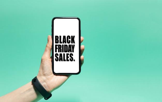 남성 손에 스마트 폰에 흰색 화면에 검은 금요일 판매 텍스트의 클로즈업. 녹청, 아쿠아 menthe 색상의 배경입니다.