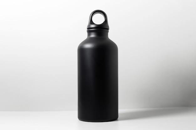 白の壁に水のための黒の再利用可能なアルミニウムエコ魔法瓶のクローズアップ。