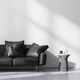 콘크리트 바닥과 흰색 벽이 있는 밝은 방에 금속 커피 테이블이 있는 검은색 소파, 빈 벽 조롱, 3d 렌더링