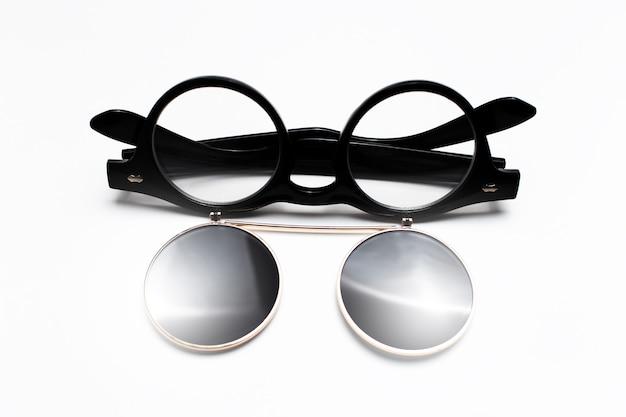 白い表面に黒いサングラスのクローズアップ。
