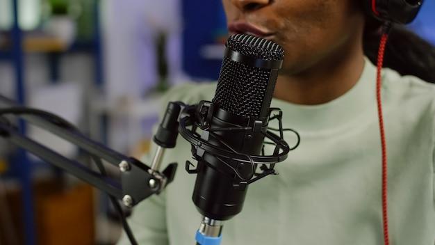 마이크를 사용하여 청취자와 논의하는 동안 청중의 질문에 대답하는 흑인 여성 인플 루 언서의 닫습니다