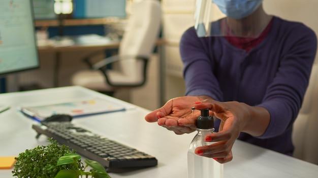 새로운 일반 회사 직장에서 사무실에서 일하는 동안 손 소독제를 사용하는 흑인 여성의 클로즈업. 코로나 바이러스에 대한 알코올 젤을 사용하여 소독 손을 청소하는 아프리카 직원.