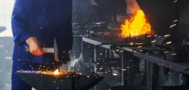 重いハンマーで金属を鍛造する鍛冶屋のクローズアップ