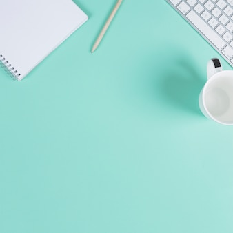 Close-up of blank notepad; pencil; cup and keyboard on turquoise background with space for text