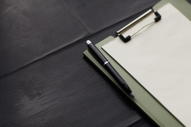 나무 테이블에 펜으로 클립 보드에 빈 종이의 클로즈업