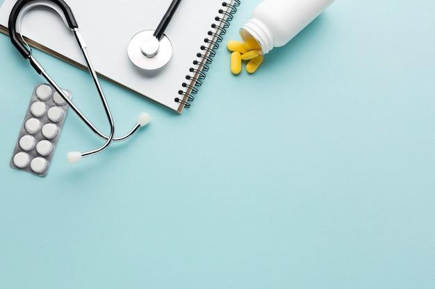 ブリスター包装された薬のクローズアップ。聴診器;青い背景上のスパイラルメモ帳