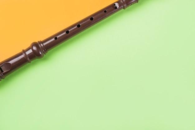 Крупный план блочной флейты на двойном оранжевом и зеленом фоне