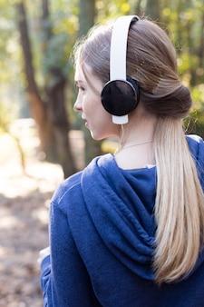 야외에서 음악을 듣고 금발 여자의 근접 촬영