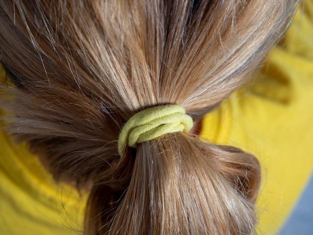 黄色のゴムバンドでお団子に結ばれたブロンドの髪のクローズアップ