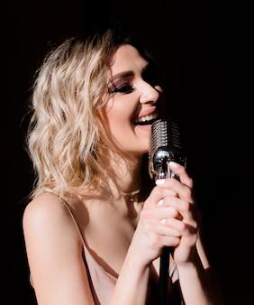 マイクを持って、孤立した黒い背景で歌う金髪の女性のクローズアップ