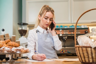 Close-up of blonde young bakery shop owner taking phone order
