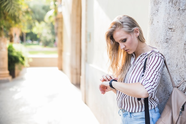 Крупным планом блондинка молодая женщина, проверка ее время на часы