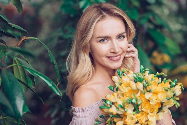 黄色の花の花束を持つ金髪の若い女性のクローズアップ