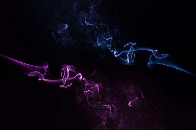 黒を背景に旋回する青と紫の煙のクローズアップ