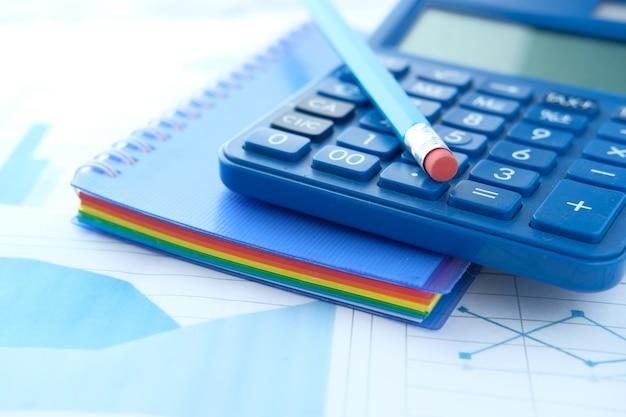 Крупным планом синий калькулятор и блокнот на цветном фоне