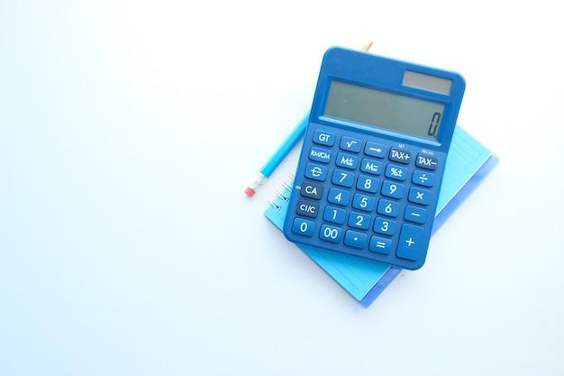 Закройте вверх синего калькулятора и блокнота на белой таблице.