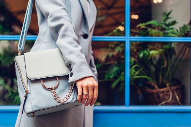 블루 여성 핸드백의 클로즈업입니다. 야외에서 가죽 가방을 들고 있는 여자. 세련된 액세서리 및 의류
