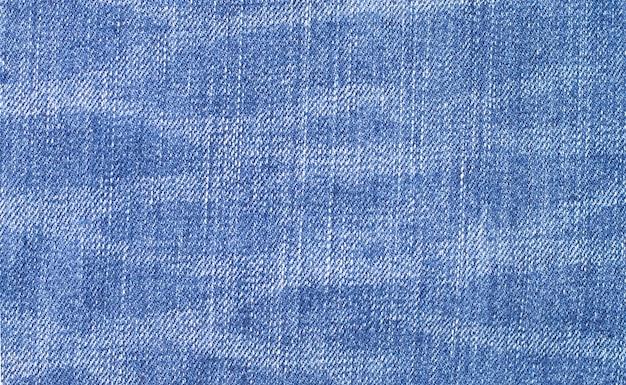 Закройте вверх текстуры синих джинсов для стены.