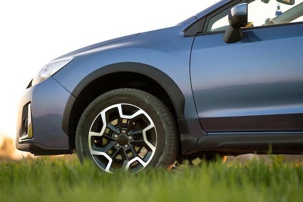 푸른 잔디에 파란색 오프로드 자동차 닫습니다. 자동차 여행, 야생 동물 모험, 원정대 또는 suv 자동차로의 극한 여행. 일출 필드에 오프로드 4x4 차량입니다.