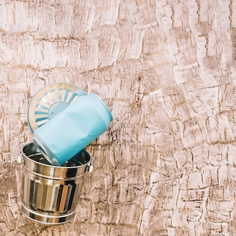 Close-up of blue tin can over metal dustbin