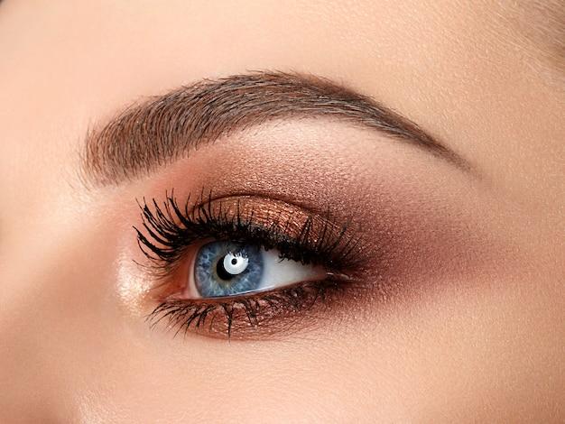 赤とオレンジの色合いのスモーキーアイメイクで美しい茶色の青い女性の目のクローズアップ。現代のファッションが構成しています。