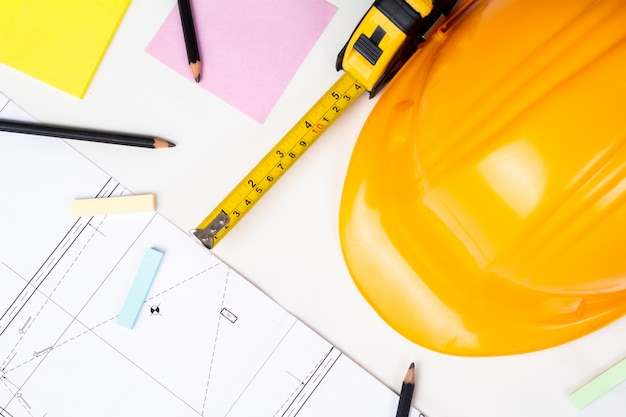 青写真、測定テープ、黄色の建設ヘルメットのクローズアップ。エンジニアのコンセプト