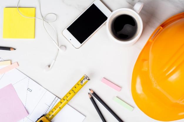 青写真、測定テープ、一杯のコーヒーと黄色の建設ヘルメットのクローズアップ。エンジニアのコンセプト