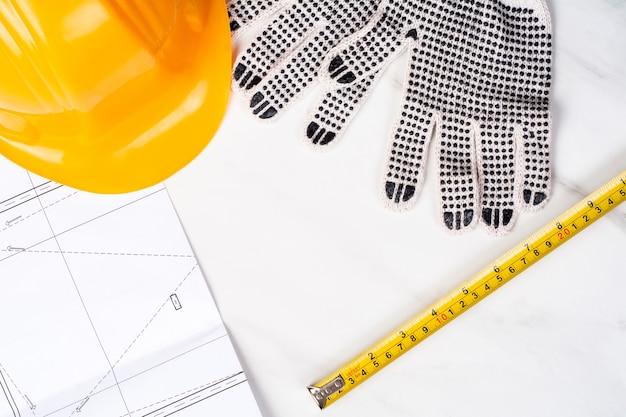 設計図、巻尺、手袋、黄色の建設用ヘルメットのクローズアップ。エンジニアの概念
